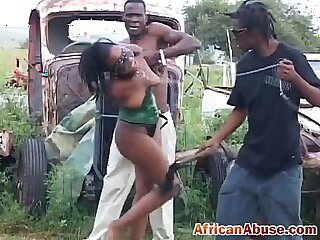 Enchained African babe gets abused by two horny guys